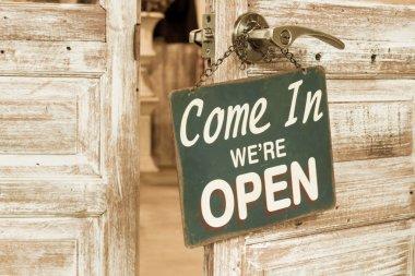 Come In We're Open on the wooden door open. Vintage retro filter