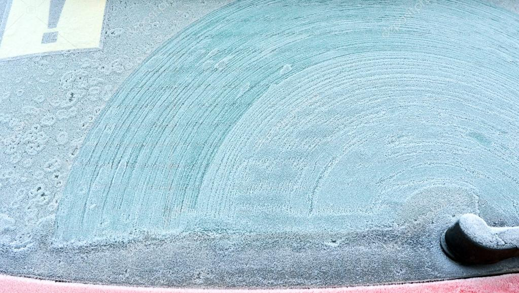 Abstract background. Screen wiper traces on frostiness car glass