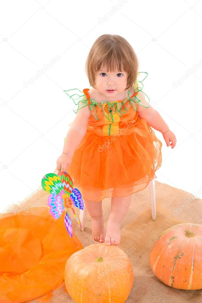 Little girl in orange costume with pumpkins