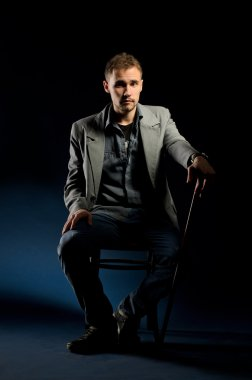 Young man with cane sitting on chair on dark background