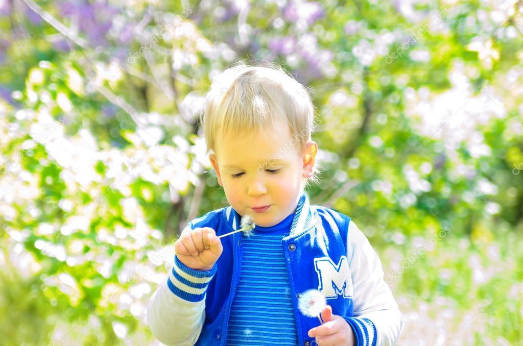 Blond boy blowing on dandelion outdoors