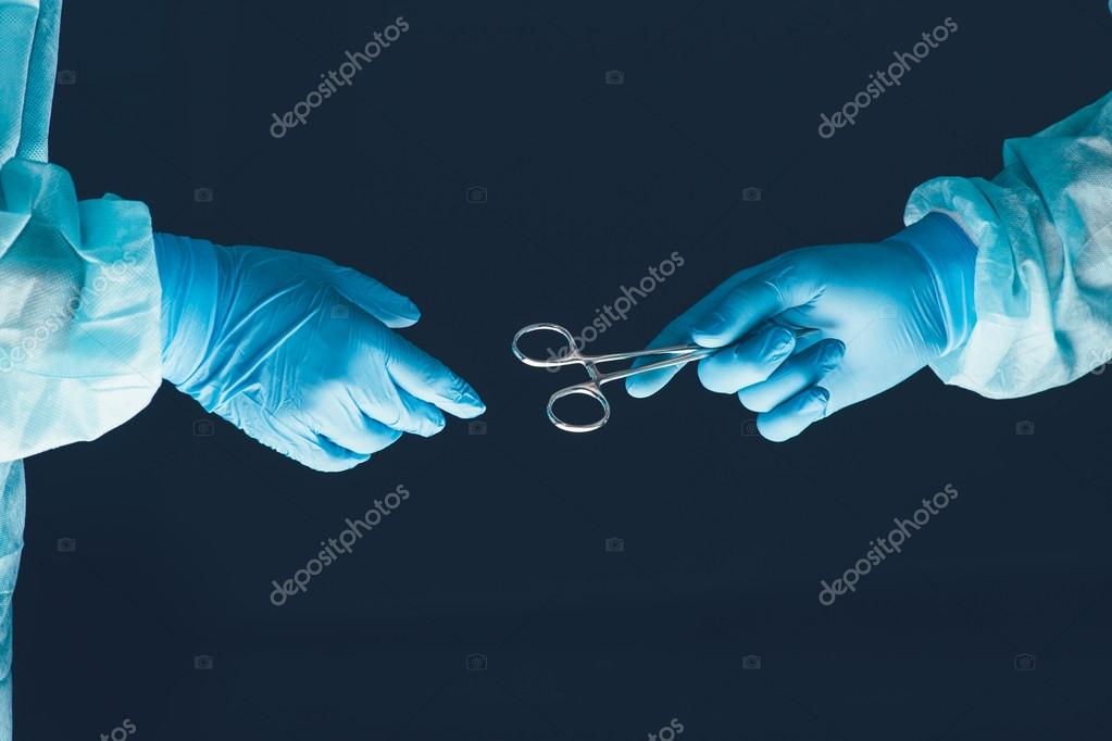 Two surgeons working and passing surgical equipment in the operating room