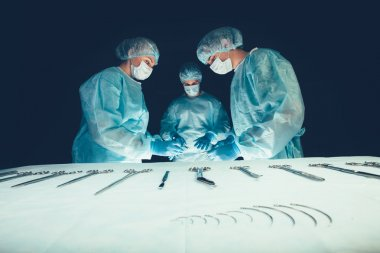 Medical team  hospital performing operation. Group of surgeon at work in operating theatre room. healthcare .