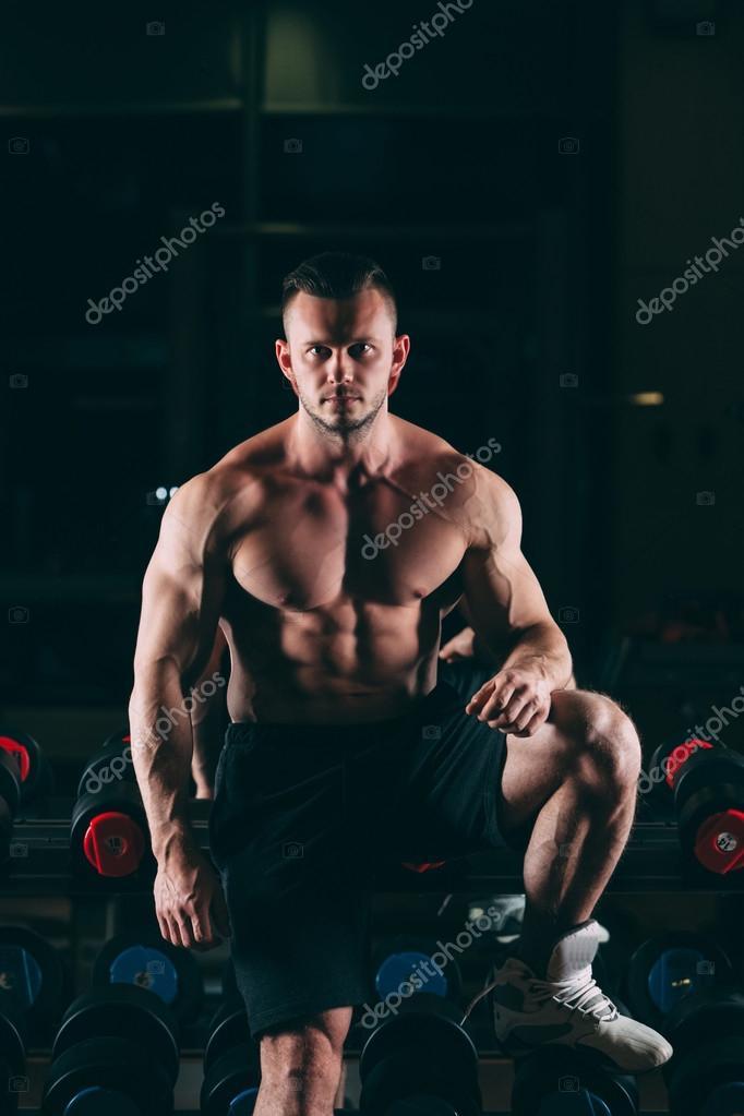 Homme musclé en gym se tenant près haltères 4c3f09809e6