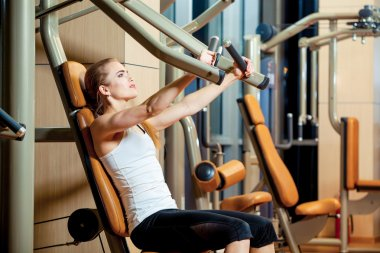 Sport, fitness, lifestyle and people concept - young woman flexing muscles on gym machine