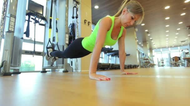 Young attractive woman does core abs crossfit oblique training with fitness trx straps in the gyms studio