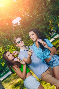 Group of friends taking picture themselves with monopod use smart phone take photograph selfie stick in park