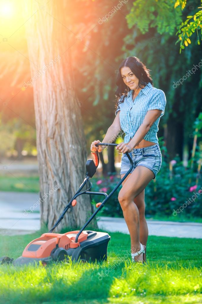Woman mowing lawn in residential back garden on sunny day