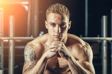 Closeup portrait of a muscular man workout with barbell at gym. He is sitting in the frame view, thinking