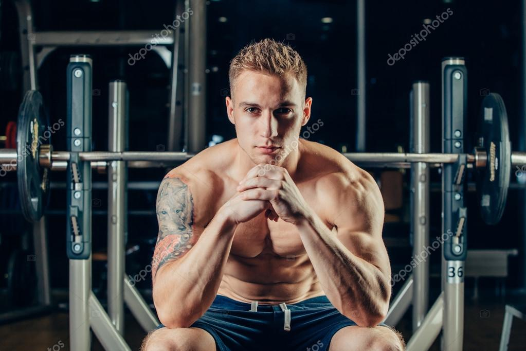 Closeup portrait of a muscular man workout with barbell at gym. He ...