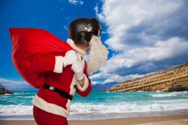 Cool Santa Claus with a bag  gifts in  Jets helmet. against background of the sea