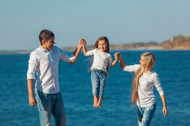 Happy family who playing on the beach. Concept of friendly familys