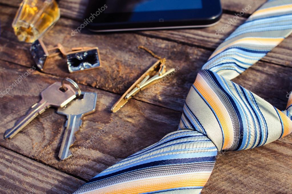 Men accessories: tie, cufflinks, tablet, perfume and keys on the old wood background