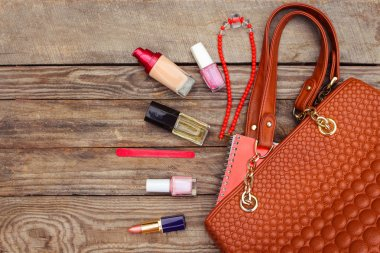 Things from open lady handbag. womens purse on wood background.