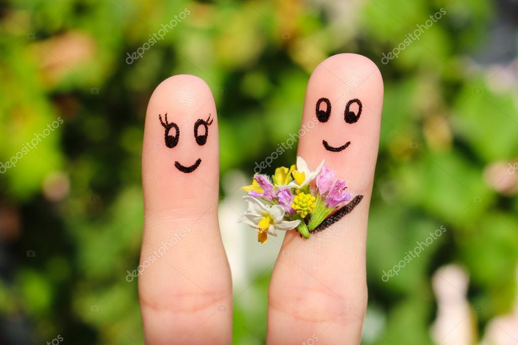 Arte del dedo de una pareja feliz. Hombre está dando flores a una ...