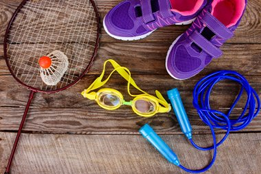 Sports equipment: the birdie is on the racket, skipping rope, swimming goggles and sneakers on wooden background