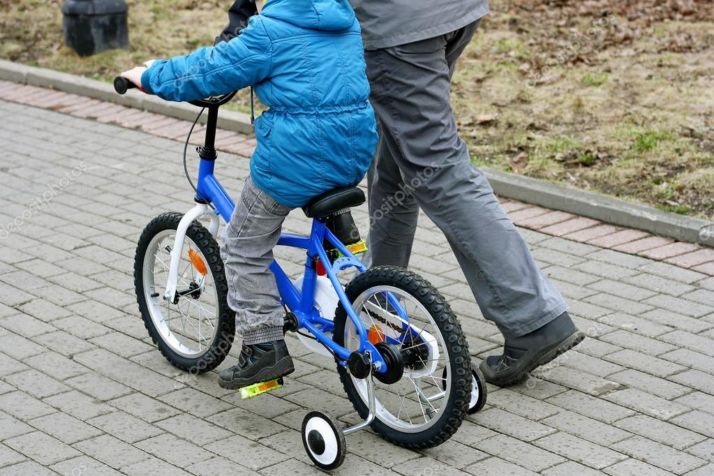 A boy with his father learning to ride a bike.