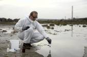 Photo Worker in a protective suit examining pollution