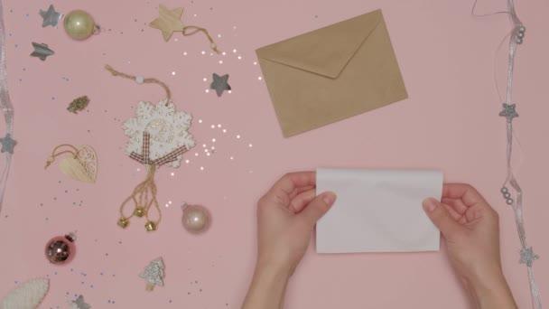 A kezek letesznek egy papírlapot, egy levelet egy gyönyörű kézműves borítékba..