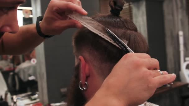 A male Barber cuts the hair on the clients head using scissors and a comb.