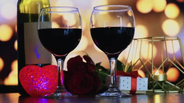 Two glasses of red wine, a candle in a gold holder, and a bouquet of red roses.