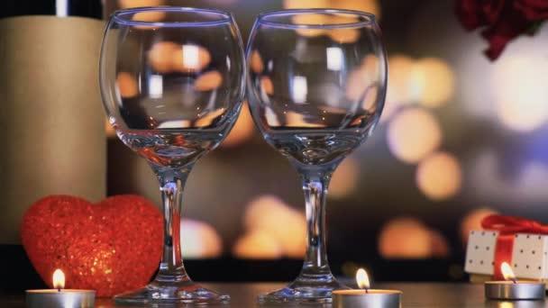 Dvě sklenice a láhev vína. Ruka položila na stůl kytici růží.