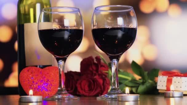 Dvě sklenice červeného vína, láhev a hořící svíčky. Valentýn.