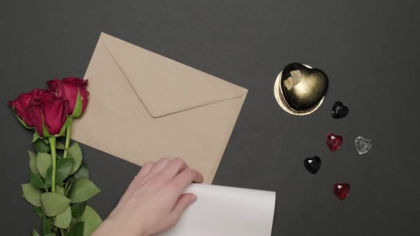 A womans hands half-fold a love letter and put it inside the envelope.