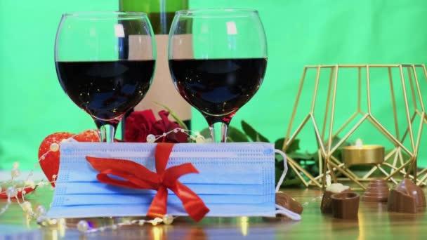 Dvě sklenice červeného vína s lékařskou maskou v dárkové stuze.