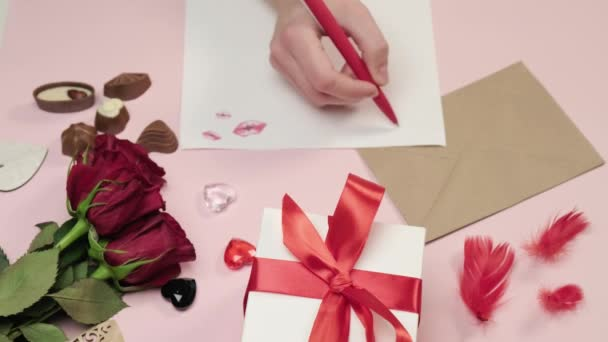 A womans hand writes a love letter on paper with a pen. Pink background.
