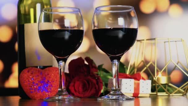 Dvě sklenice vína a svíčku ve zlatém držáku a kytici rudých růží.
