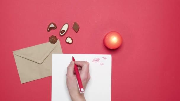 Egy nő levelet ír papírra, szerelmes levelet és kézműves borítékot..
