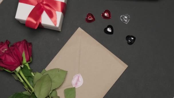 On the dark table is a letter with a kiss. Gift in a box and a bottle of wine.