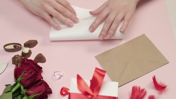 A woman hand arranges a love letter on paper in an envelope. Bouquet of roses.