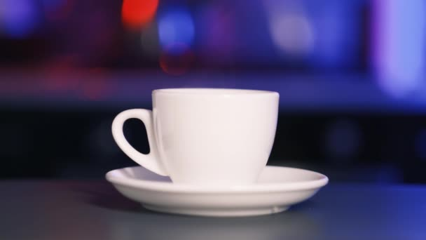 On the table is a white cup and saucer from which comes the aroma of coffee.