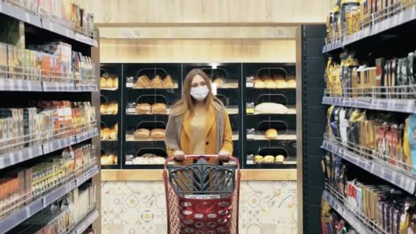 A young woman walks with a shopping cart and selects products in a medical mask.