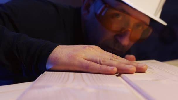 Ein männlicher Bauarbeiter mit Schutzhelm fährt mit der Hand über das Brett.