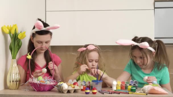 Three girls paint Easter eggs with paint and paint brushes. 4k video.