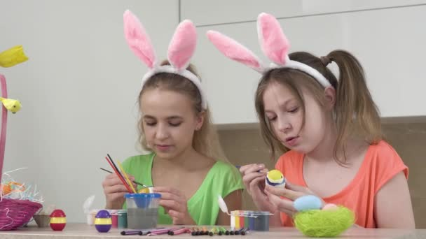 Two girls with bunny ears decorate Easter eggs together and talk. Easter holiday