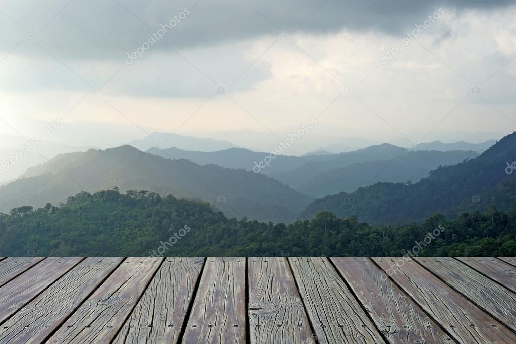 Wooden floor with misty mountain hills landscape, layers of mountains with fog background