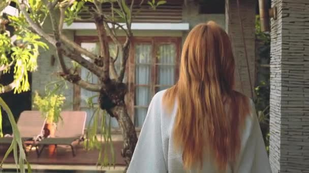 Mladá žena v županu k dveřím vily