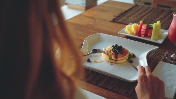 Borůvkové palačinky, ovoce, džus a kávu na dřevěný stůl