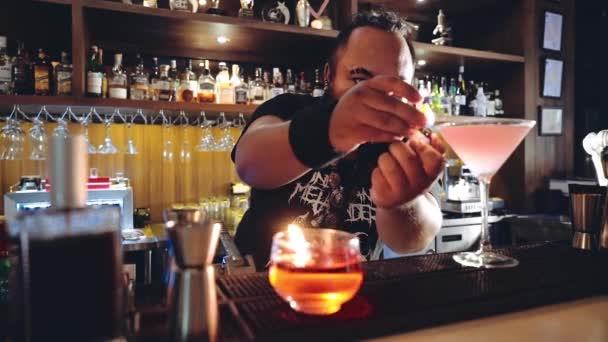 Barman with piercings finishing cocktail, placing it in front of camera, smiling