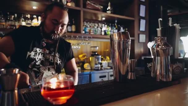 Bartender with piercings and dreadlocks putting ice into glass