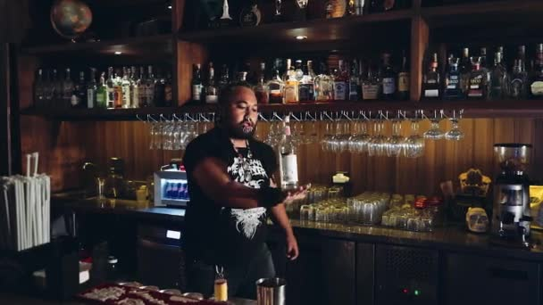 Bartender with piercings and dreadlocks practices juggling bottle