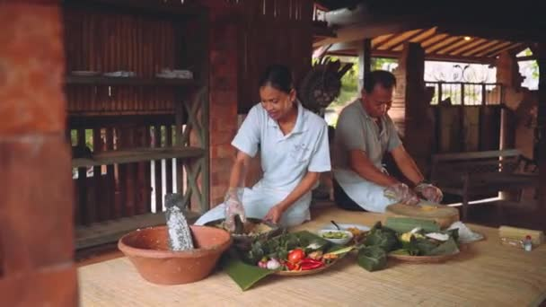 Traditional balinese cooking: grating coconut, grinding with mortar and pestle