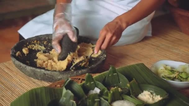 Grinding corn with mortar and pestle, other ingredients nearby in palm leaves