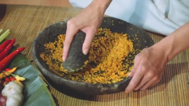 Grinding with Pestle and Mortar on cooking class, other ingredients nearby