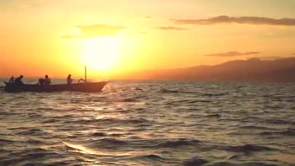 Dolphins jumping in front of boat with 3 people