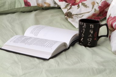Black mug with a black book on the bed linens flowered